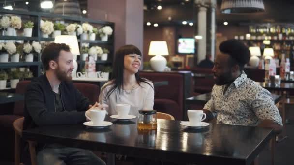 multi-ethnic company of friends in a cafe or restaurant. friends talk and have fun together.