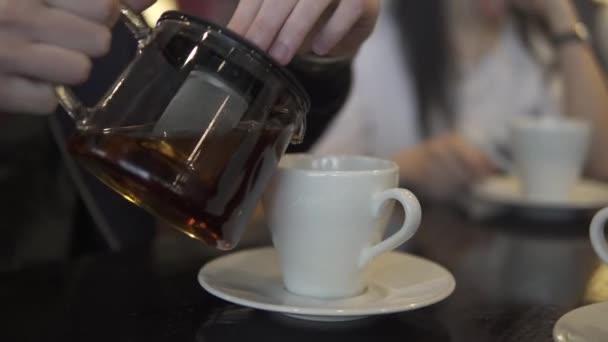 muž nalévá čaj z sklenici do hrnku
