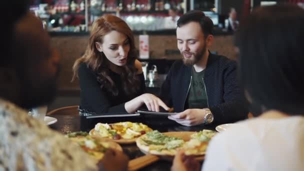 company of friends together spend time at lunch in the restaurant. the guy and the girl choose dishes from the menu.