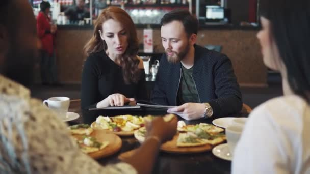 guy and the girl choose dishes from the menu. company of friends together spend time at lunch in the restaurant