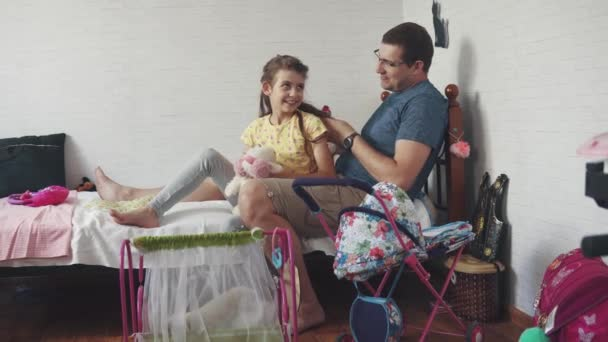 The young father combs his daughter with a toy comb sitting on the bed in the childrens room. Dad and daughter spend time together