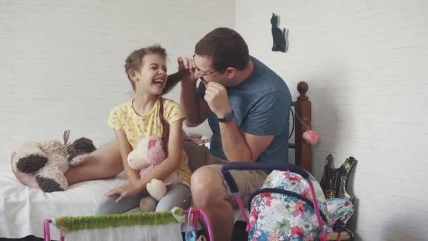 the young father spends time with his little daughter. Dad plaits pigtails to her daughter, plays with her and fools around. friendship between father and daughter.