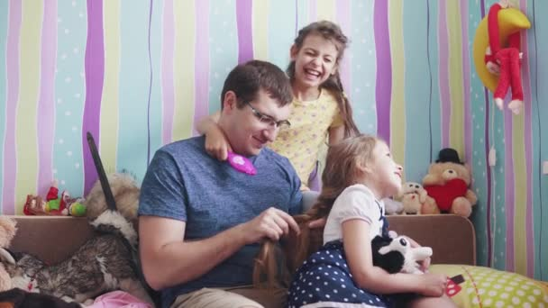 friendship of the father and daughters. young daddy does pigtails daughters