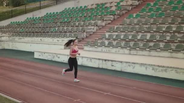 antény. tenké sportovní dívka jogging na stadionu. atraktivní mladá žena cvičení venku