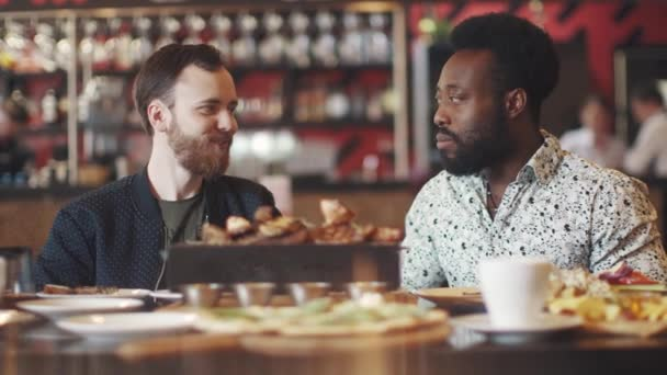 a multi-ethnic group of friends in a restaurant. two friends at a table in a cafe