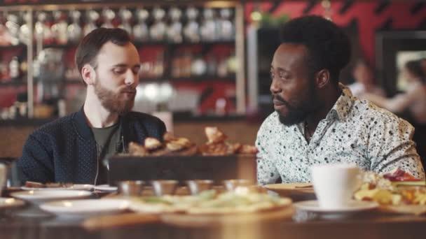 dva mladí muži jíst steak v restauraci. dva přátelé sedí u stolu v útulné restauraci a bavte se mluví. přátelskou večeři