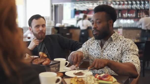 two young men eat a steak in a restaurant. two friends sit at a table in a cozy restaurant and have fun talking.