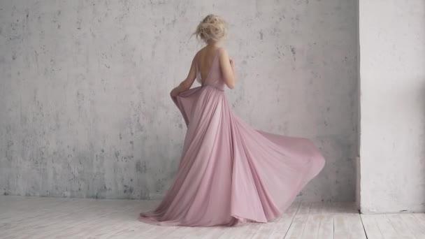 die charmante Blondine im Abendkleid dreht sich und ihr Kleid flattert. Porträt eines attraktiven Mädchens mit festlichem Make-up und Frisur.