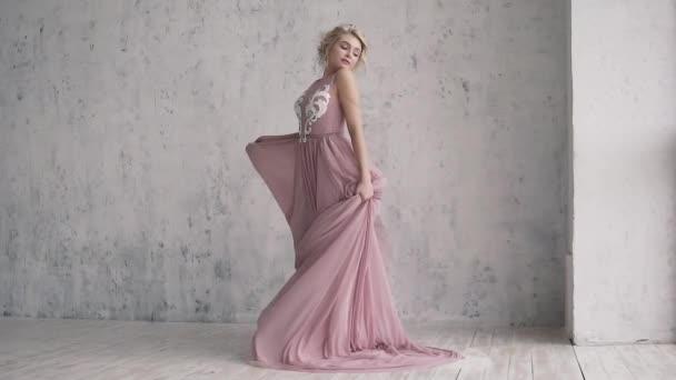Okouzlující blondýnka ve večerních šatech se točí a vlající šaty. portrét atraktivní dívka s slavnostní make-up a účes.