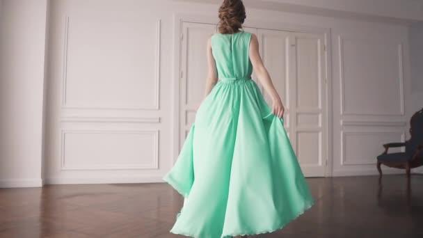 egy fiatal lány zöld ruhában. portréja egy vonzó brunette szép smink és frizura. spinning egy ruha lány. lassú mozgás