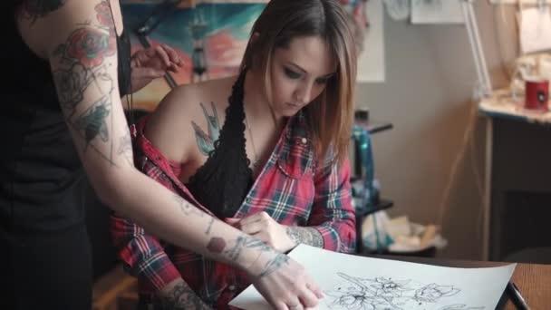 tetováló művész tárgyalja egy ügyfél vázlat tetoválás. tetováló mester házi stúdiójában