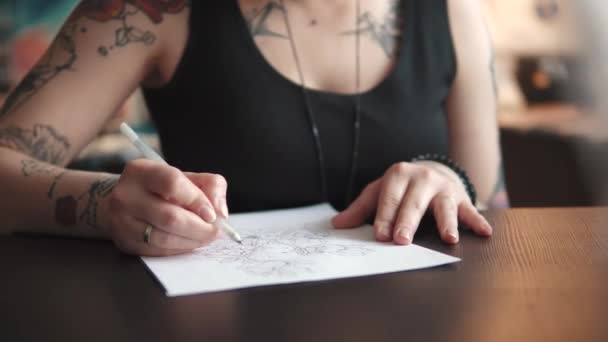 tattoo artist makes a sketch of tattoo on paper in a home Studio