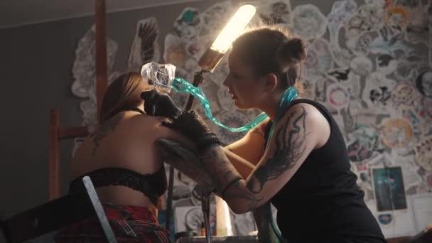 hlavní tetování dělá tetování v domácím studiu. dívka tattooist pracovní tetování stroj v domácím studiu. holka dělá tetování na rameno
