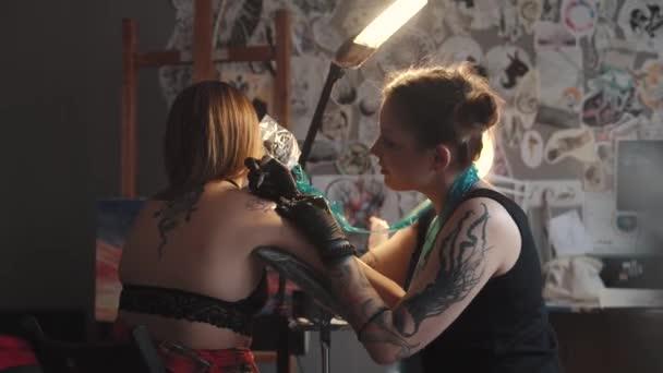 rajz a tetoválás a vállán közelről. mester tetoválás ideiglenes tákolmány egy rotációs tetoválás géppuska