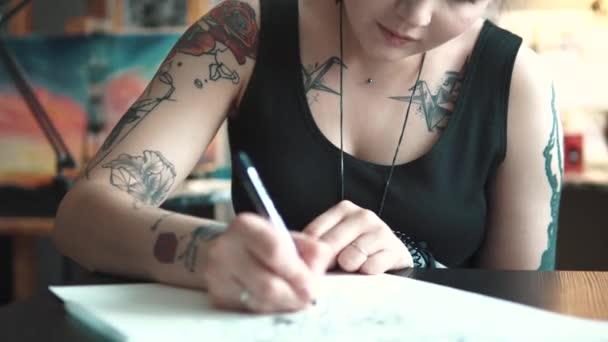 Tattoo umělec dělá nákres tetování na papíře v domácím studiu