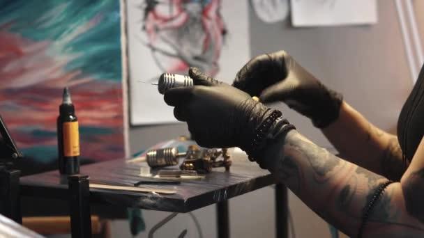 tetováló művész gyűjti a tetoválás gép. lány tetoválás mester készül egy rotációs tetoválás géppuska rajz rajz a bőrön
