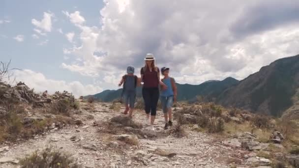 family of tourists. a young woman with children walking along a path in the mountains. A young mother and children with backpacks go on a hike. back view