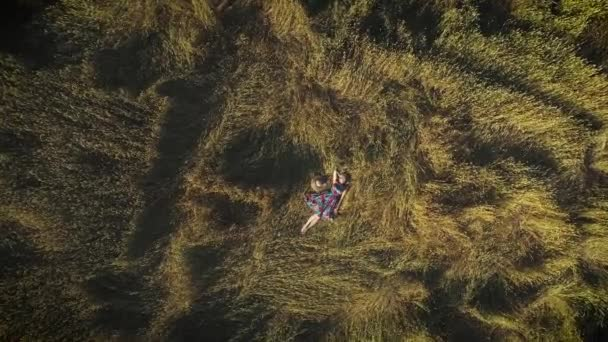 aerial. attractive girl in a rustic dress lies in the hayloft. young woman in a hat. The concept of unity with nature and tranquility. view from above.
