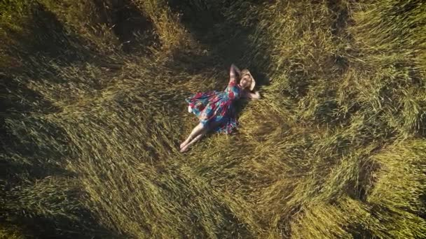 aerial.girl lying on the grass with his hands behind his head. a pretty woman in a rustic dress in the hayloft. view from above.