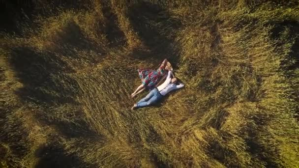 aerial. a girl and a man in casual clothes lie in the hayloft and enjoy a warm summer day. concept of friendship, love and unity. view from above.