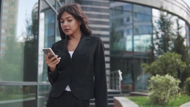 attractive business woman uses a smartphone on the background of a modern business center