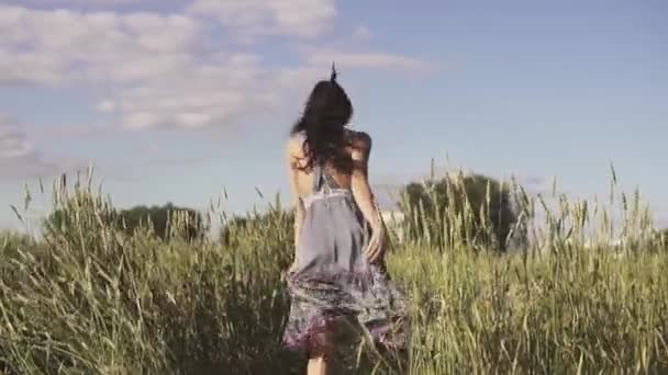 cheerful and happy girl running across the field with tall grass. slow motion