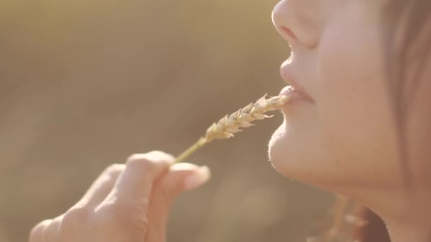 girl touches her lips with a wheat ear