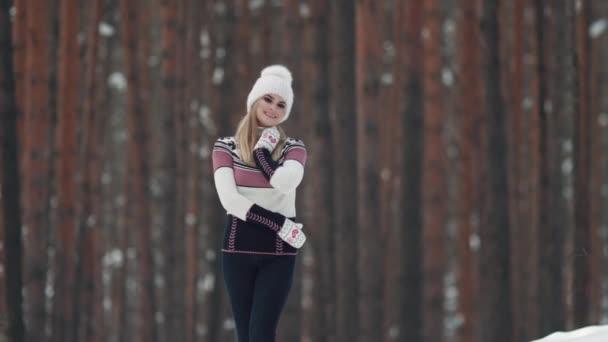 portrét atraktivní a krásná mladá dívka v palčáky pletené svetry a čepice na tmavém pozadí. Mladá žena v zimě lese