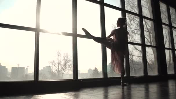 silhouette of a ballerina on the background of a large window. ballet dancer doing stretching