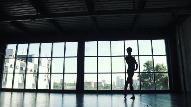 Silhouette eines Balletttänzers, der vor dem Hintergrund eines großen Fensters tanzt. tanzt die Tänzerin elegant im Studio. Zeitlupe