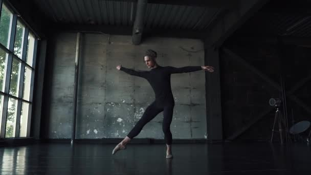 male ballet dancer dancing classical ballet in a dark studio. slow motion