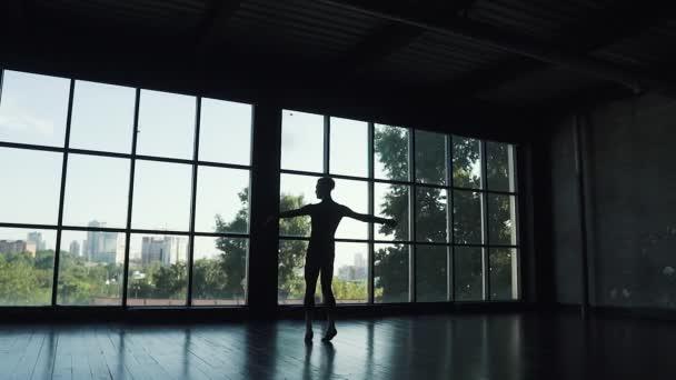 silueta baletní tanečník na pozadí velké okno. tanečník otočí na špičkách a elegantně pohybuje. Zpomalený pohyb