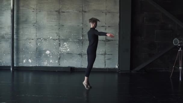portrait of a young male ballet dancer dancing in the studio. slow motion