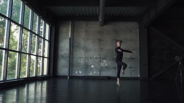 oung férfi balett-táncos klasszikus balett tánc stúdió, sötét háttér előtt. lassú mozgás