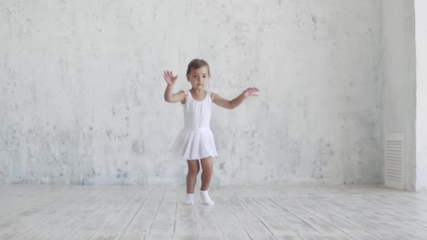 a small ballerina in a white pack jumps up. slow motion