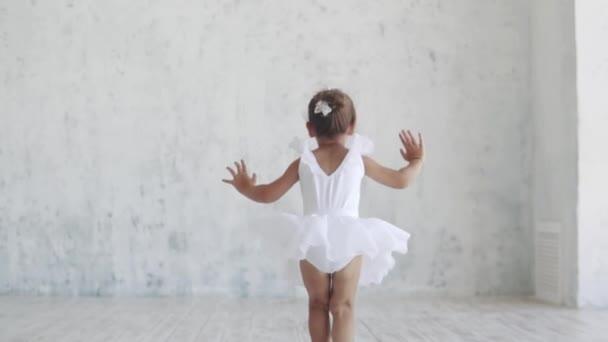 springt eine kleine Ballerina im weißen Rudel auf. Zeitlupe. zurück
