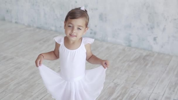 close-up portrait of a child in a white ballet tutu. Little girl smiles and looks at camera