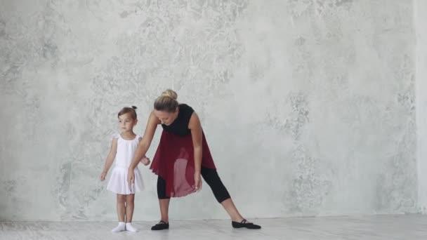 kleine Ballerina wiederholt die Bewegung in ihrer Ballettstunde für ihren Lehrer