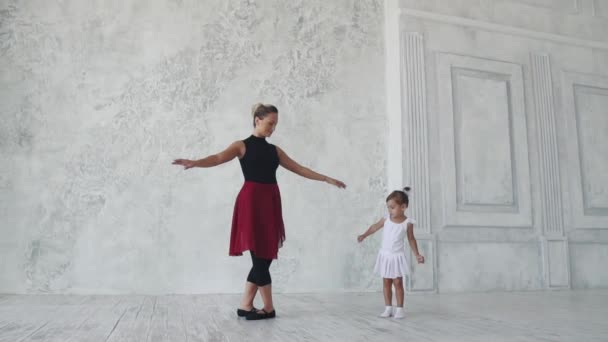 trochu legrační dívka se snaží opakovat pohyby za baletka v baletu třídy. Zpomalený pohyb