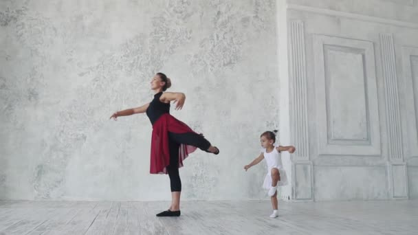 Ein kleines lustiges Mädchen versucht, die Bewegungen hinter der Ballerina in der Ballettstunde zu wiederholen. Zeitlupe