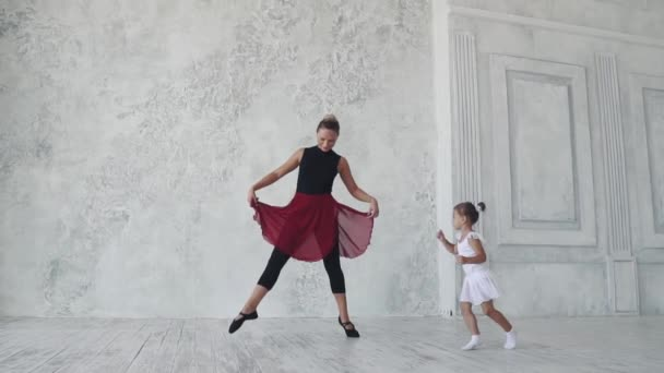 ballet lesson. a little ballerina in a tutu dances funny with her teacher. slow motion