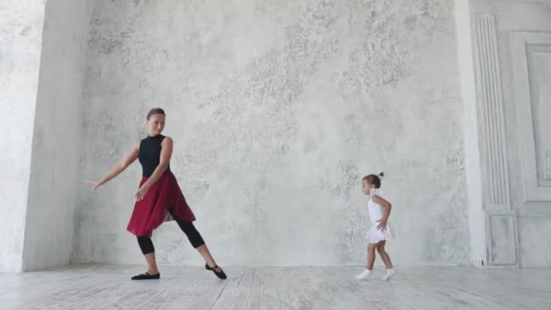 malá baletka v tutu baletní třídy. baletu učitel a student holčička tančí spolu. Zpomalený pohyb