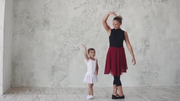 malá baletka opakuje pohyby za učitele. lekce baletu v ateliéru