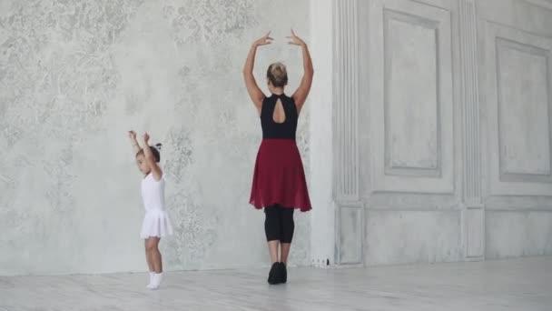 malá baletka s jejím učitelem ve třídě baletu. baletka se točí na špičkách