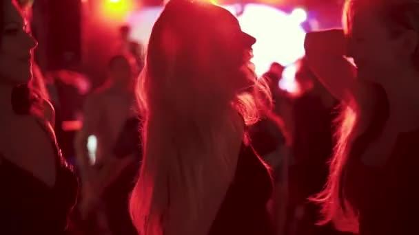 amici che ballano nei raggi di riflettori rossi ad una discoteca in un locale notturno. ragazze che ballano in mezzo alla folla di persone