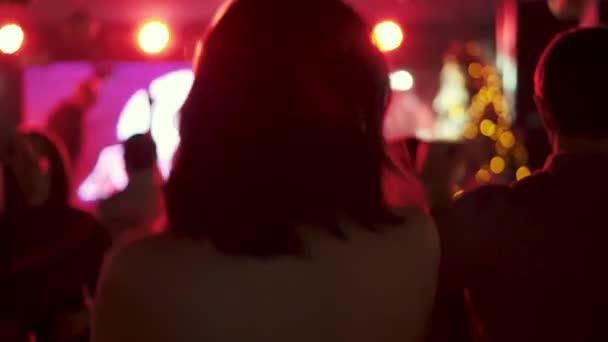 portrét mladé dívky tančí v disco na pozadí dav lidí. pohled z zadní.