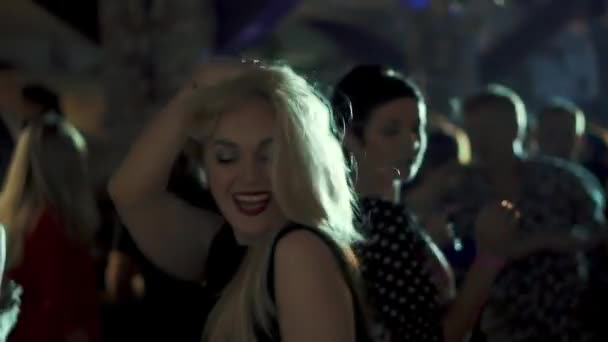 Mädchen tanzen auf einer Party. Porträt einer jungen Frau, die unter anderen Menschen tanzen.