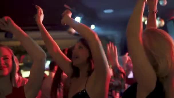 a lányok tánc, figyelemfelkeltő kezüket fel. a fiatal nők a partin