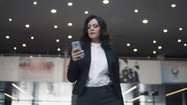 Obchodnice s chytrým telefonem v ruce je chůze v hale moderní kancelářské budovy. portrét dívky v obleku.