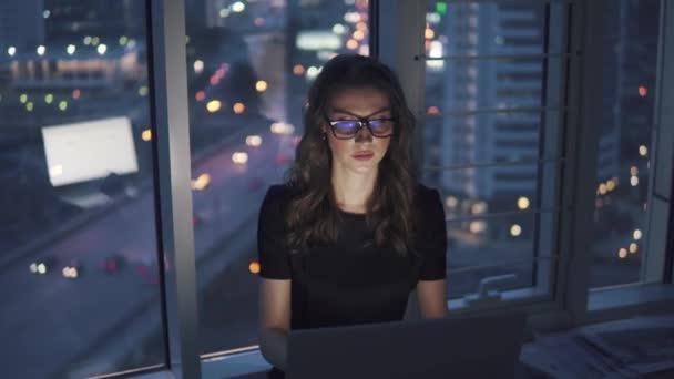 lány dolgozik az office késő este háttere az éjszakát a város fényei. fiatal üzletasszony szemüveg monitor tükröződéssel